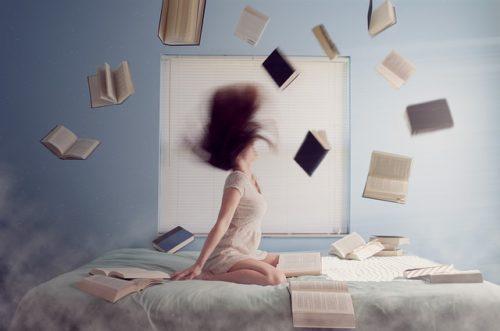 Étudiante assise sur un lit entourée de livres volant autour de sa tête