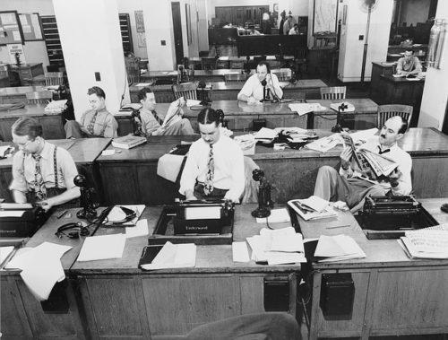 Photographie en noir et blanc d'une rédaction de quotidien où les journalistes semblent se tourner les pouces...