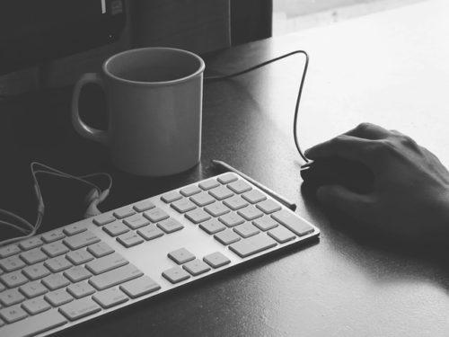 Main sur une souris d'ordinateur, à côté d'un clavier et d'une tasse de café
