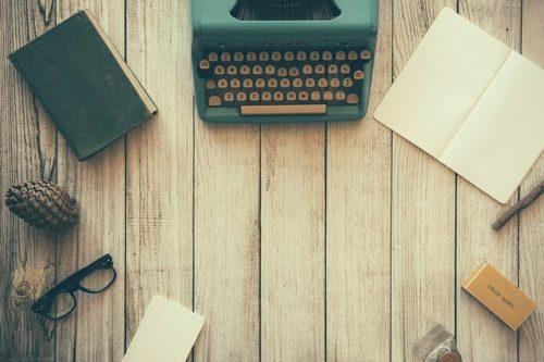 Photo d'une table avec une machine à écrire, des carnets, et une paire de lunettes...