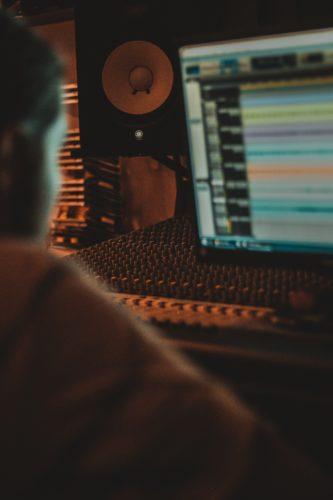Photographie d'un jeune homme devant un écran affichant des pistes sonores, manipulant les curseurs d'une table de mixage.