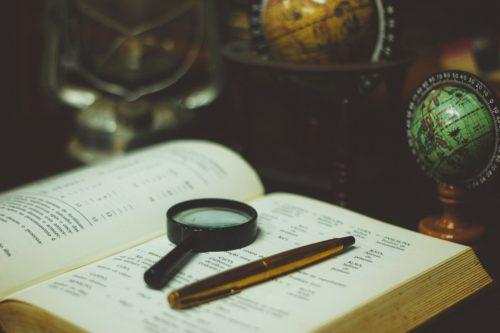 Image d'une loupe et d'un stylo posés sur un ouvrage ancien, à côté d'un globe terrestre.